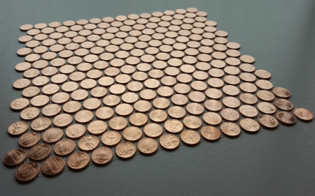 Tile sheet of shiny pennies only, viewed on an angle.