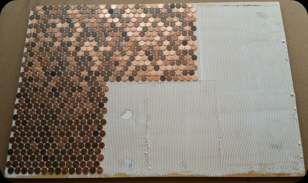 Sheets of pennies being installed on floor with adhesive.