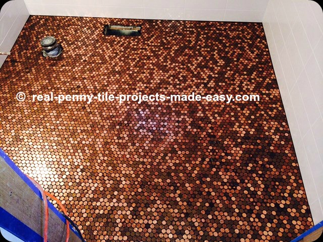 Handmade sheets of real pennies installed on bathroom floor as the ultimate penny round mosaic tile.