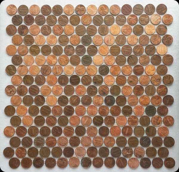 Standard tile sheet of real random pennies on mesh.