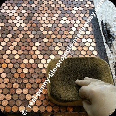 Washing/cleaning the black sanded grout from the surface of pennies. Cleaning started almost immediately after spreading the grout, to avoid grout drying hard on pennies.