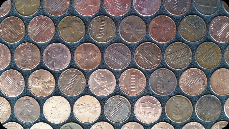 Close-up on black-grouted pennies installed as tile sheets on floor.