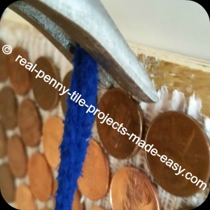 Pennies as tile on wall - installation strength check close-up.
