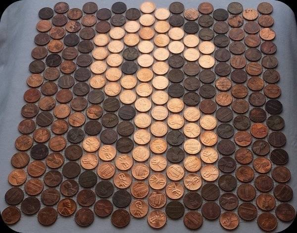 Dollar sign made with money... new shiny pennies among darker random pennies on mesh as mosaic tile.