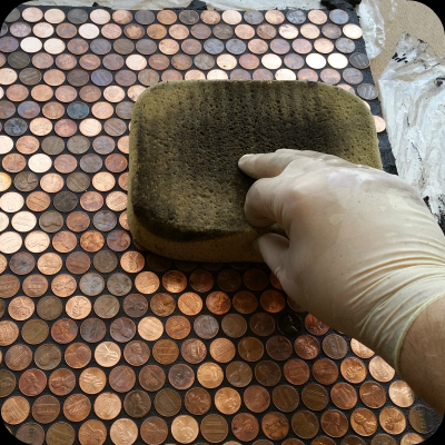 Using sponge to clean grout from floor of pennies.