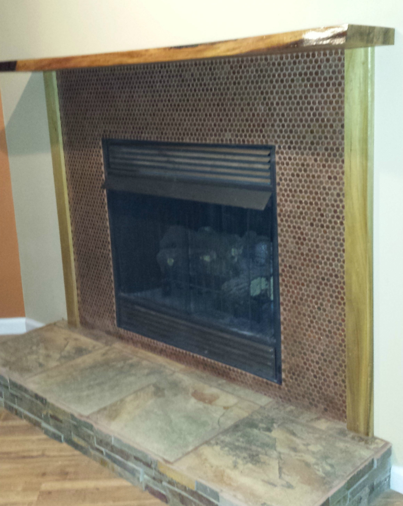 Fireplace wall covered with penny tile sheets (pennies).