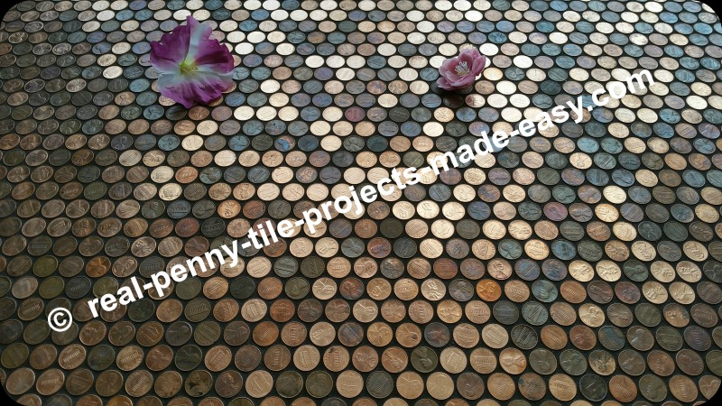 Flowers on grouted floor of pennies.
