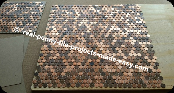 Four sheets of pennies placed down on plywood.