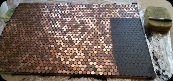 Grout application to pennies on floor.