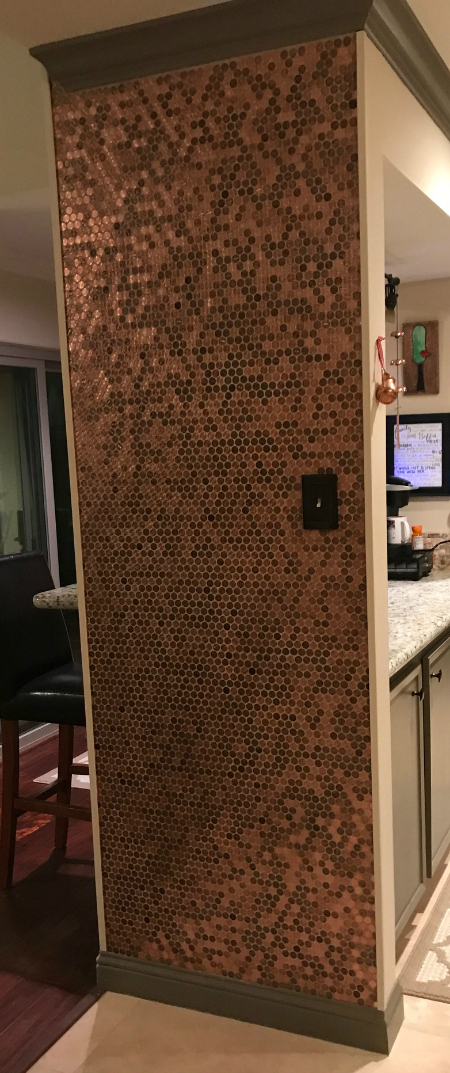 Pennies as mosaic tile sheets installed on a kitchen wall from floor to ceiling.