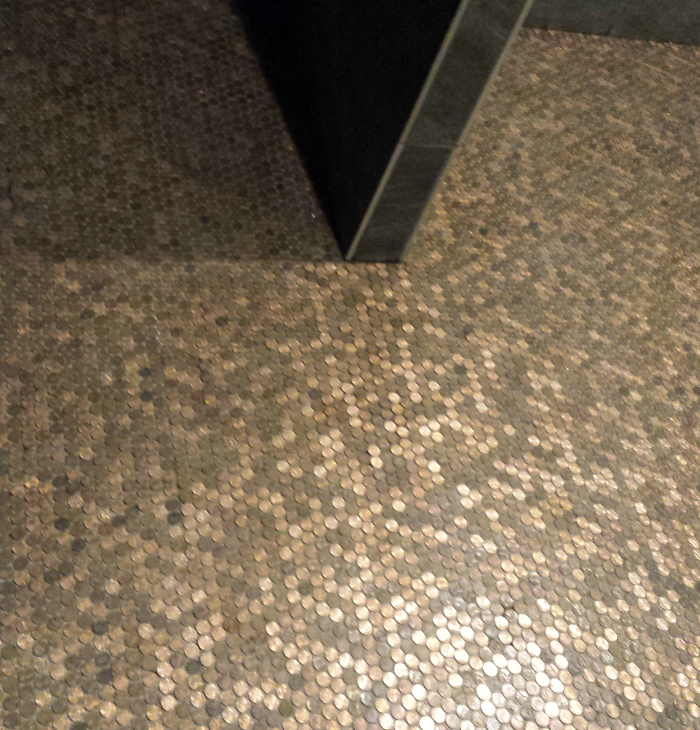 Floor covered in tile sheets of pennies. Picture taken before grouting.