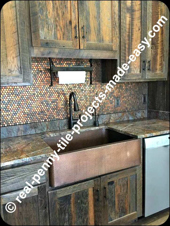 Rustic kitchen decor with real pennies on backsplash, antique looking cabinets, copper sink, dark faucet, matching theme countertops and other rustic characteristics.