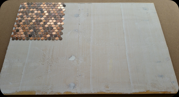 Pennies being placed on floor with adhesive.