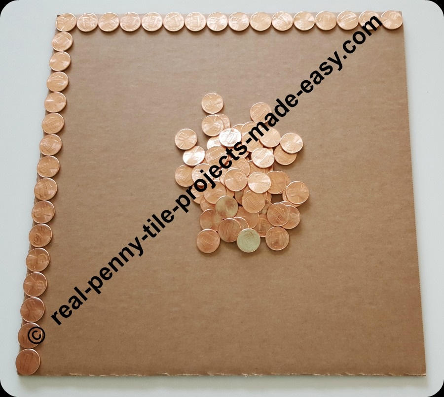 2 sides of a square foot cardboard having pennies on them.