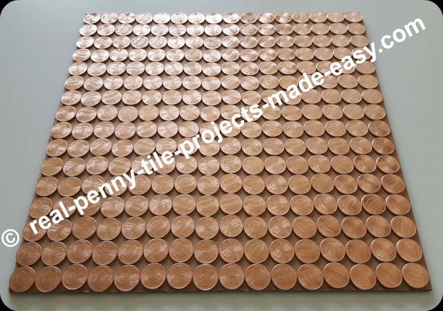 Angle view of 256 brand new pennies sitting on a square foot cardboard in straight rows.
