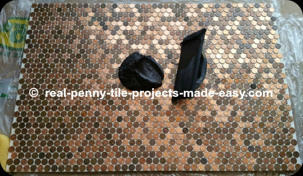 Black sanded grout about to be applied to pennies installed as tile on floor.