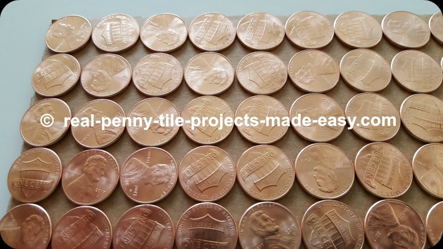 Close-up on straight rows of pennies showing empty room in between them.