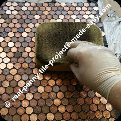 Using damp sponge to clean grout from floor of pennies.