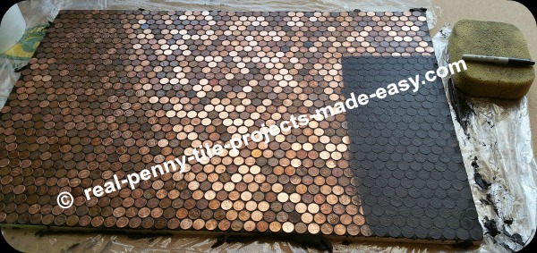Grout application and cleaning of pennies on floor.