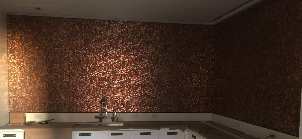 Backsplash made with random pennies on our standard real penny tile. Wall covered in sheets of pennies from countertop to ceiling.