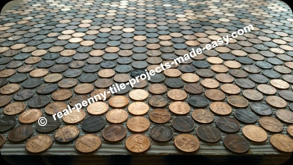 Six sheets of pennies glued to floor with adhesive.